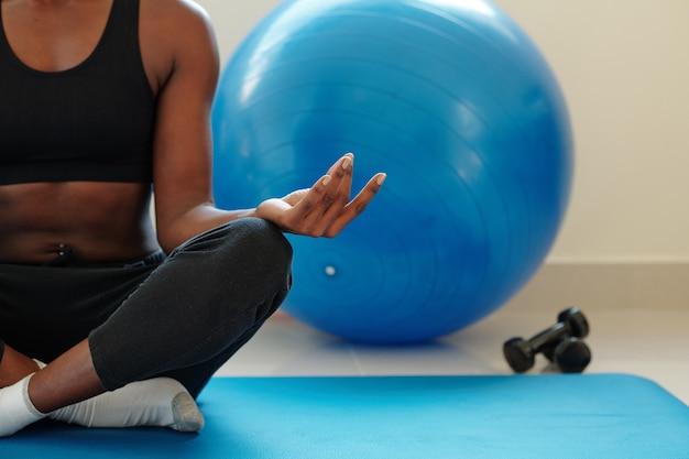 Обрезанное изображение подтянутой молодой женщины, медитирующей в позе лотоса после тренировки с гантелями и фитнес-мячом