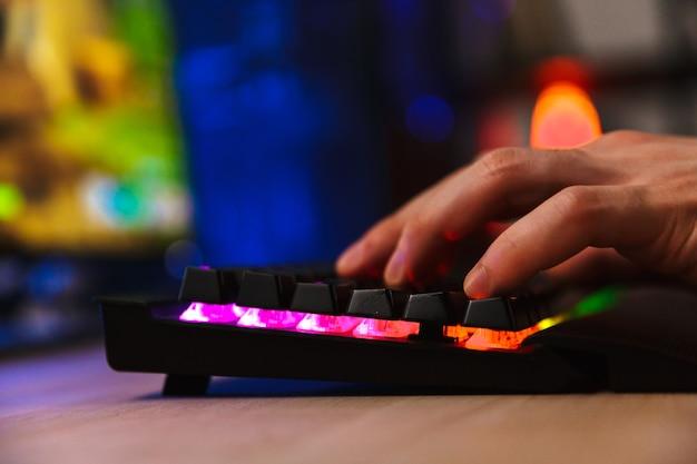 Обрезанное изображение геймера, играющего в видеоигры на компьютере