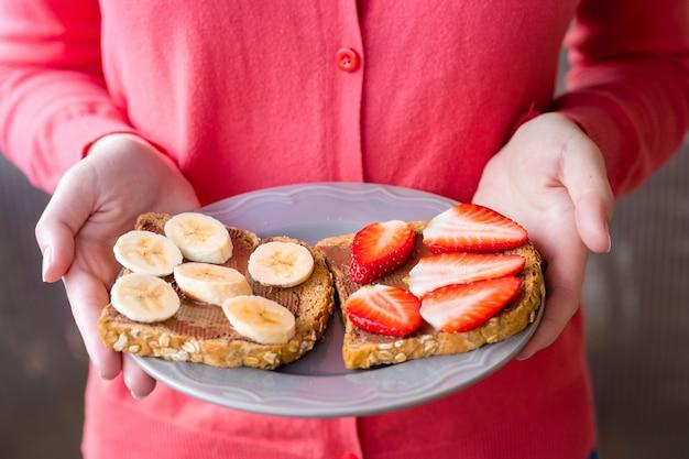 Обрезанное изображение девушки, держащей тарелку с тостами из шоколадной пасты и фруктов