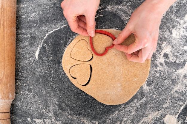 Обрезанное изображение девушки, делающей тесто в форме сердца