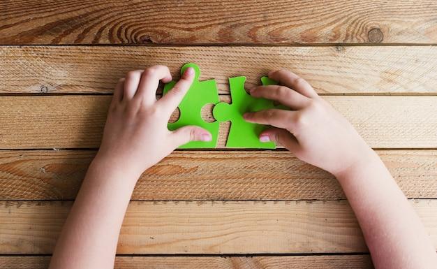 나무 테이블에 두 개의 퍼즐 조각을 연결하는 손의 자른 이미지