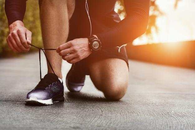 운동 화 실행 표면 배경에 구두 끈을 묶는 손의 자른 된 이미지 스포티 한 운동 화에 구두 끈을 묶는 보수계와 스포츠맨의 손 실행 장비 개념 신발 끈 묶는