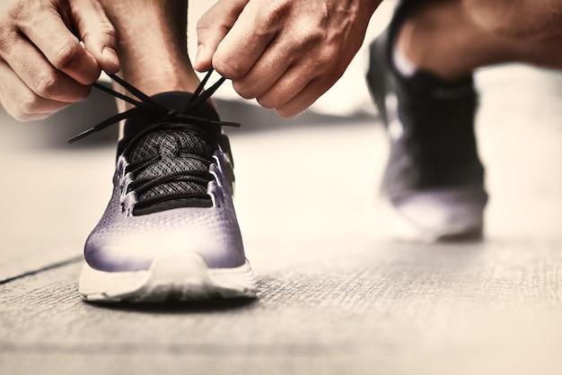 スニーカーのランニング面の背景に靴紐を結ぶ手のトリミング画像スポーティなスニーカーに靴紐を結ぶ歩数計を持つスポーツマンの手ランニング機器のコンセプト靴紐を結ぶ