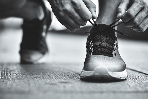 운동 화 실행 표면 배경에 구두 끈을 묶는 손의 자른 이미지 스포티 한 운동 화 실행 장비 개념에 구두 끈을 묶는 보수계와 스포츠맨의 손