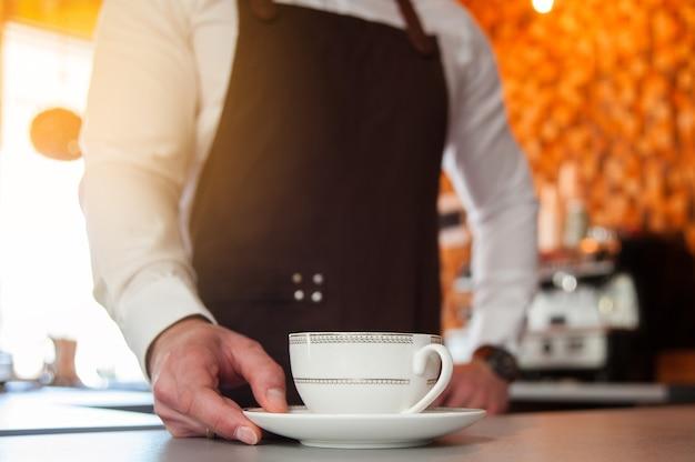 カフェのバーカウンターで一杯のコーヒーを保持しているエプロンのハンサムなバリスタのトリミングされた画像。