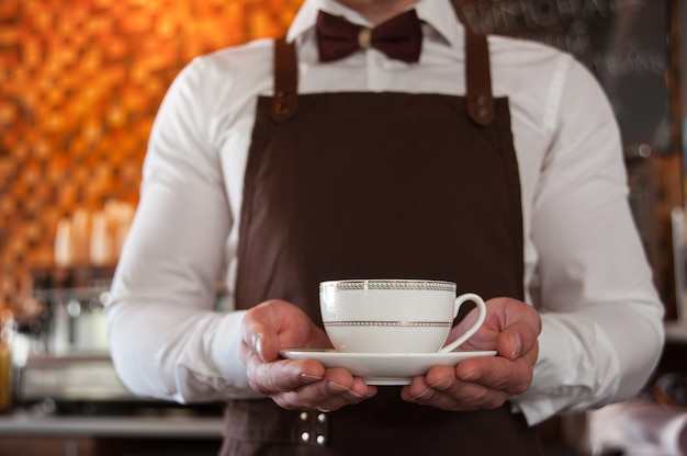 Обрезанное изображение красивый бариста в фартуке, держащий чашку кофе за барной стойкой в кафе.