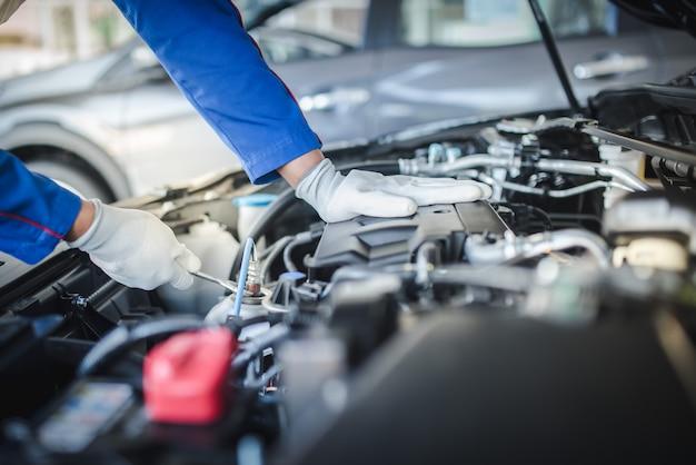 制服を着たハンサムなメカニックのトリミングされた画像は、自動車サービスで働いています。車の修理とメンテナンス。