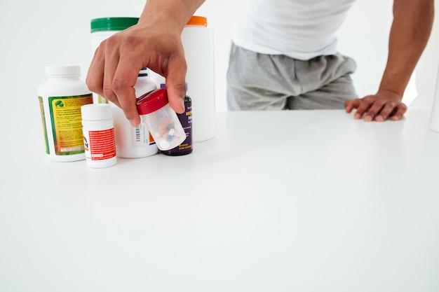 Обрезанное изображение красивый молодой спортсмен, держа витамины