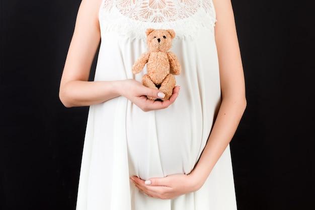 검은 배경에서 그녀의 배꼽에 테디 베어를 들고 흰 드레스에 행복 한 임신한 여자의 자른된 이미지. 기대하는 아이. 공간을 복사합니다.