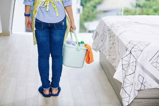 寝室に立っているcleanig洗剤のバケツと主婦のトリミングされた画像