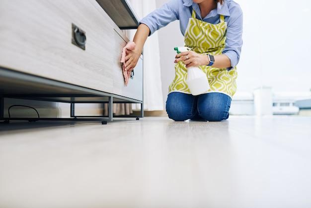 Обрезанное изображение домохозяйки, дезинфицирующей ящики в гостиной специальным моющим средством