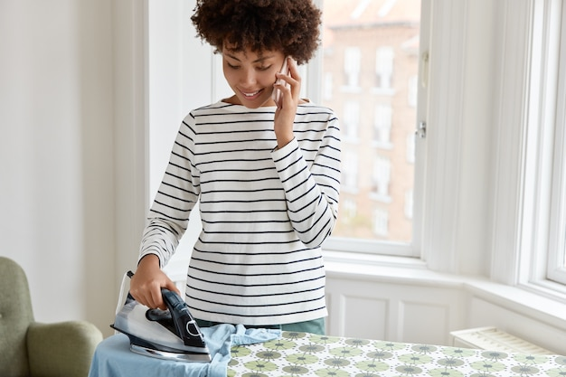 Обрезанное изображение домохозяйки разговаривает по телефону во время утюга дома на выходных