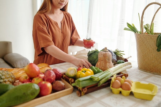 スーパーで買った野菜や果物の袋を開梱する主婦のトリミング画像