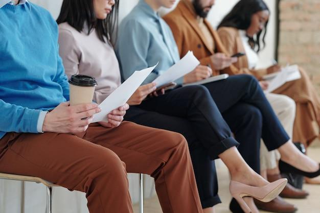 Обрезанное изображение межрасовых кандидатов, сидящих с бумагами в ряду и готовящихся к собеседованию
