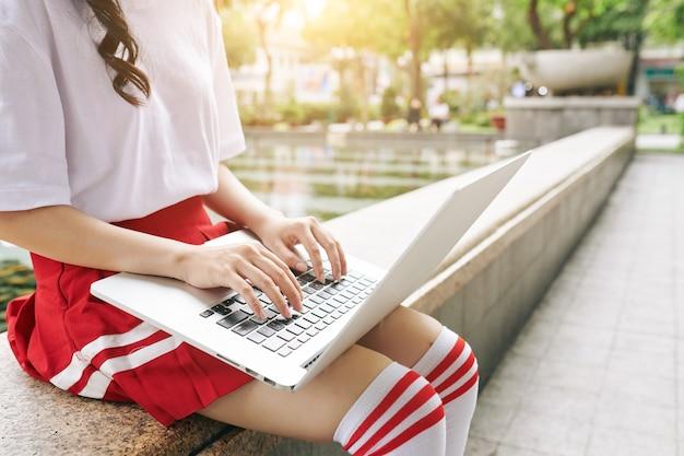 キャンパスでラップトップで作業している制服を着た韓国の女子高生のトリミングされた画像