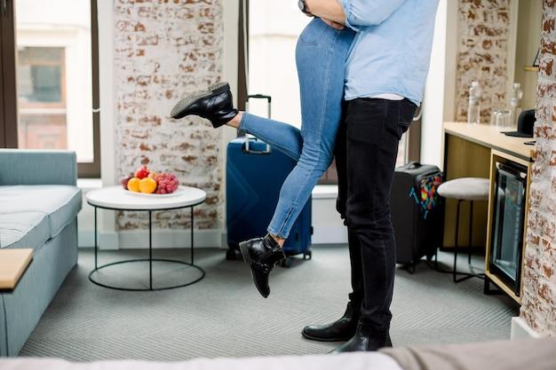 Обрезанное изображение ноги молодых влюбленных в повседневной одежде, проводить романтическое время вместе, обниматься в гостиничном номере. мужчина держит женщину на руках