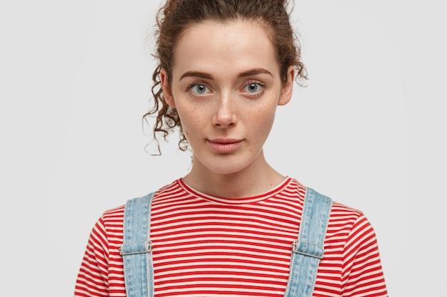 素敵な若い緑色の目の巻き毛の女性のトリミングされた画像は、真剣に見え、カジュアルな服を着て、白い壁に隔離された何かを注意深く聞いています。そばかすのある女性のクローズアップ