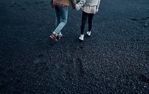 Обрезанное изображение влюбленной пары туристов, взявшись за руки, развлекаются во время прогулки по пляжу с черным вулканическим песком. путешествия, отдых, туризм.