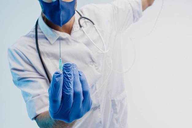 Обрезанное изображение мужского доктора показывает шприц. человек со стетоскопом в белом халате, защитной маске и латексных перчатках. изолированные на сером фоне с бирюзовым светом. студийная съемка. скопируйте пространство.