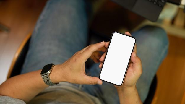 Обрезанное изображение мужчины, держащего мобильный телефон, отправляющего текстовые сообщения, загружающего макет пустого экрана приложения
