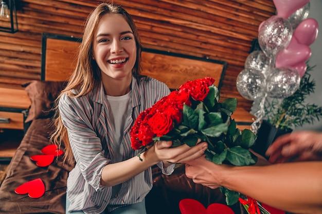 남자의 자른 이미지는 여자에게 빨간 장미를 제공합니다.