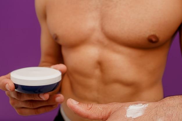 Обрезанное изображение человека держать контейнер с косметическим кремом. косметический крем на мужской руке. концепция ухода за кожей лица. изолированные на фиолетовом фоне. студийная съемка