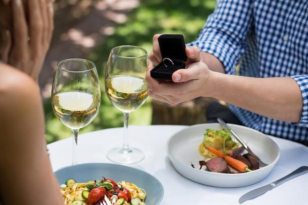 야외 레스토랑에서 여자에게 약혼 반지를 보여주는 남자의 자른 이미지