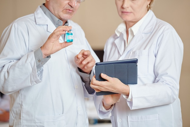 タブレットコンピューターでcovid-19ワクチンの読書記事を持つ医療従事者のトリミングされた画像