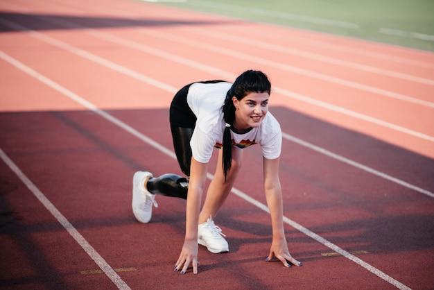 Обрезанное изображение мотивированной женщины-спортсмена-инвалида с протезом ноги, делающей упражнения на растяжку сидя