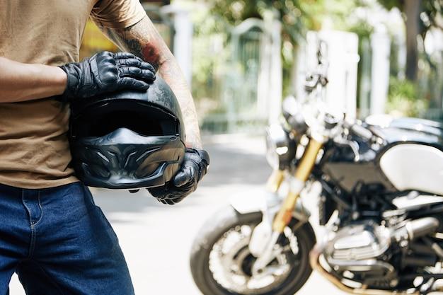 Обрезанное изображение мотоциклиста в кожаных перчатках, держащего шлем, на заднем плане - его велосипед