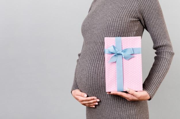 회색 배경에서 그녀의 배꼽에 대 한 임신 한 여자의 손에 분홍색 발견 된 선물 상자의 이미지를 잘립니다. 회색 드레스에 미래의 어머니입니다. 여자 아기를 기다리고 있습니다. 공간 복사