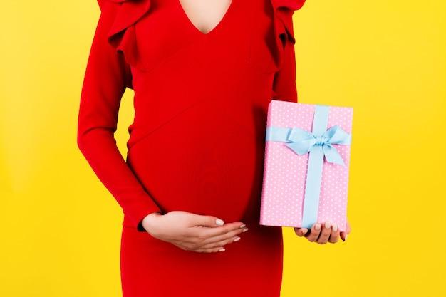 노란색 표면에서 그녀의 배꼽에 임신 한 여자의 손에 분홍색 발견 선물 상자의 자른 이미지