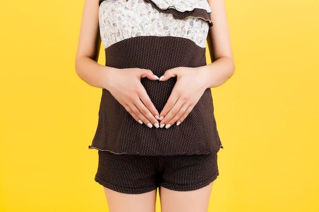 아기 범프에 하트 모양으로 손을 잡고 있는 임산부의 자른 이미지