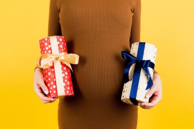 노란색 배경에 두 개의 선물 상자를 들고 갈색 드레스에 임신한 여자의 자른 이미지. 소년인가 소녀인가? 쌍둥이를 기다립니다. 임신 축하. 공간을 복사합니다.