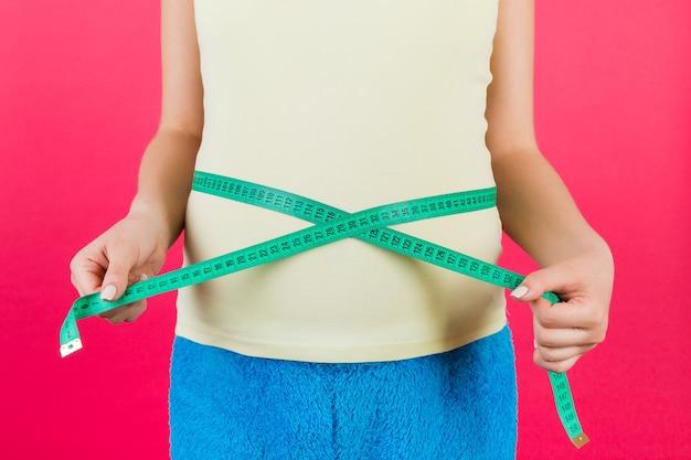 赤ちゃんの発達をチェックするために彼女の腹部を測定するカラフルな家庭服の妊婦のトリミングされた画像