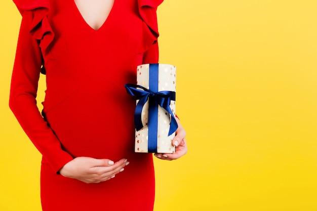 선물 상자를 들고 노란색 표면에서 그녀의 아랫 배를 만지고 빨간 드레스에 임신 한 여자의 자른 이미지
