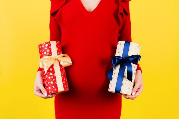 노란색 배경에 두 개의 선물 상자를 들고 빨간 드레스에 임신한 여자의 자른 이미지. 소년인가 소녀인가? 쌍둥이를 기다립니다. 임신 축하. 공간을 복사합니다.