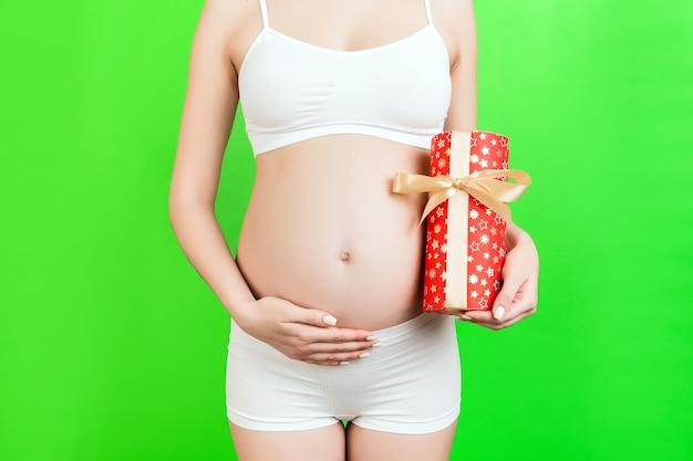 선물 상자를 들고 녹색 배경에서 그녀의 아랫 배를 만지고 흰색 속옷에 임신 한 여자의 자른 이미지. 여자 아기를 기대하고 있습니다. 공간을 복사하십시오.