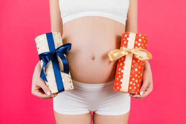 분홍색 배경에 두 개의 선물 상자를 들고 흰 속옷에 임신한 여자의 자른 이미지. 그것은 소년 또는 소녀 쌍둥이를 기다리고 있습니다. 임신 축하. 공간을 복사합니다.