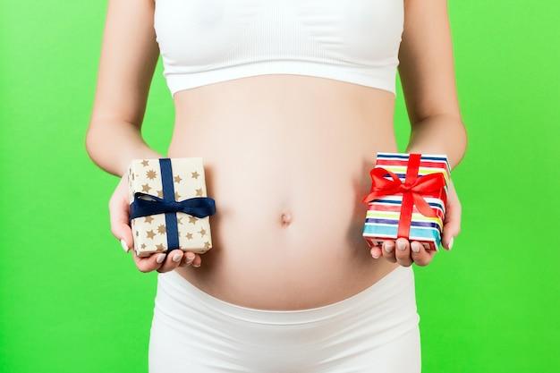 두 개의 선물 상자를 들고 흰 속옷에 임신 한 여자의 자른 이미지