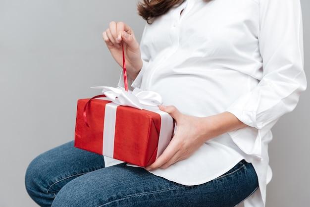 Обрезанное изображение беременной женщины с подарком в студии изолировал серый фон Premium Фотографии