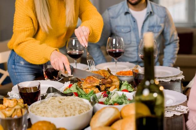 かなり若い母親の画像をトリミングして感謝祭のディナーに家族のために七面鳥を切る