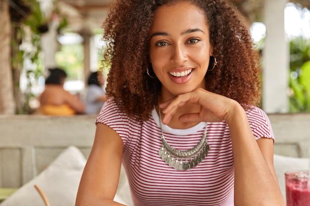Обрезанное изображение симпатичной молодой девушки-подростка с темной кожей, свежими волосами, держащей руку под подбородком, одетой в повседневную одежду, позирует на фоне интерьера кафе, встречается с лучшим другом, имеет свободное время на выходных