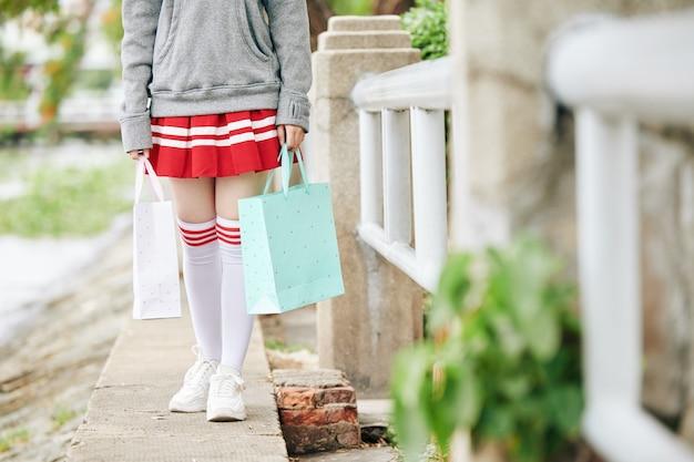 屋外を歩くときに紙袋を保持している短いスカートと太もものハイソックスの女子高生のトリミングされた画像
