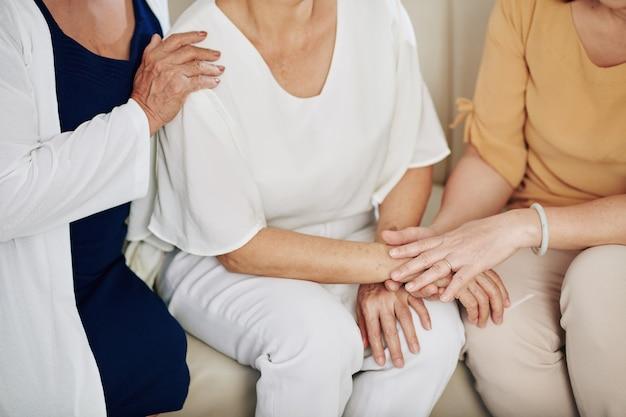 彼女を安心させるために友人の手に触れる年配の女性のトリミングされた画像