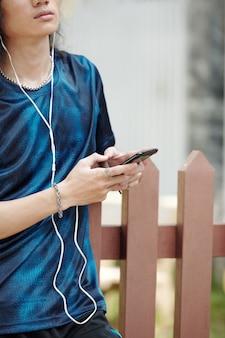 屋外を歩いているときにスマートフォンで音楽を聴いている真面目な男性のトリミングされた画像