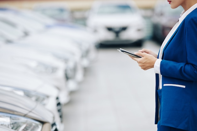 자동차 행 앞에 태블릿 컴퓨터로 서 심각한 젊은 여성 대리점 관리자의 자른 이미지