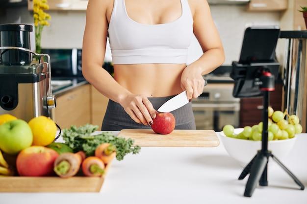 날씬한 젊은 여성의 자른 이미지는 건강한 아침 식사를 위해 사과를 자르는 자신을 촬영하기 위해 스마트폰을 설정했습니다.