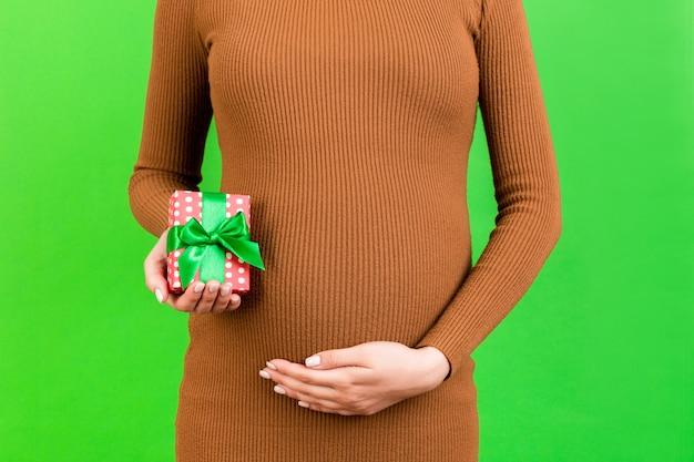 녹색 배경에서 임산부의 손에 있는 작은 선물 상자의 자른 이미지. 젊은 어머니는 갈색 드레스를 입고 있습니다. 행복한 임신. 공간을 복사합니다.
