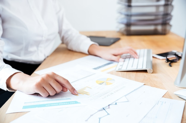Обрезанное изображение умной серьезной бизнес-леди, указывая пальцем на рабочие документы на столе и печатая на клавиатуре в офисе